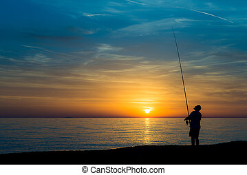 Fisherman on the beach at sunset