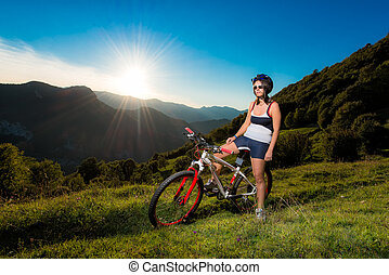 girl in mountain bike during sunset