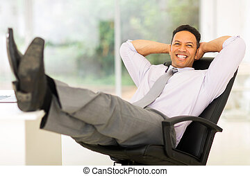 businessman relaxing in office - happy businessman relaxing...