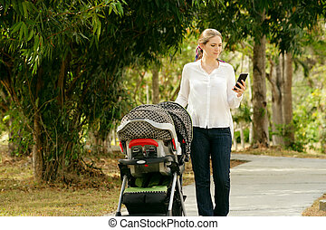 Mother With Baby In Pushchair Typing Message On Phone -...