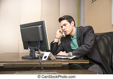 Successful handsome young businessman at desk talking on...