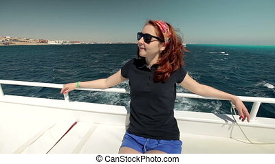 Young woman in sunglasses sits on yacht boat, enjoying sun, life and sea. Smiling and looking at clear sky