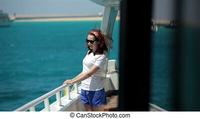 Young woman in sunglasses walk on yacht boat, enjoying sun,...