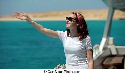 Young woman in sunglasses walk on yacht boat, enjoying sun, life and sea. Smiling and looking at clear sky