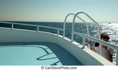 Young woman climbing up stairs on yacht boat, enjoying sun, life and sea. Smiling and looking at clear sky
