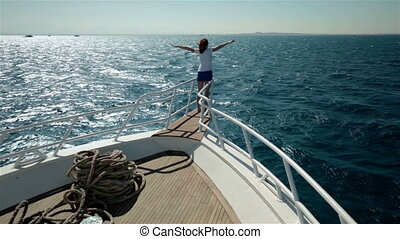 Young woman arms like bird wings on yacht boat prow, enjoying sun, life and sea. Smiling and looking clear sky