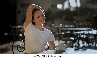 Young girl woman relaxing in cafe street veranda, drinking coffee enjoying life