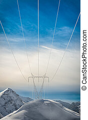 Pylons covered with snow in the high mountains carry energy...