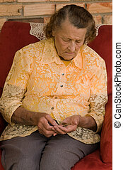 counting the cost - elderly caucasian woman counting coins...