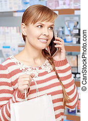 Customer of a pharmacy with paper bag - Phone consultancy....