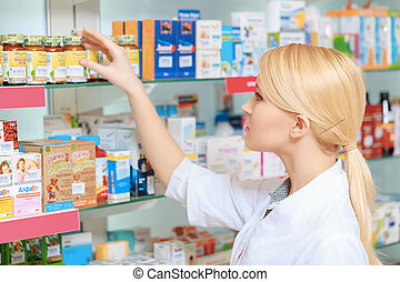 Pharmacist arranging medicines on the shelves - Searching...