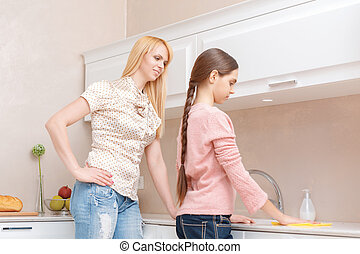 Mother and daughter cleaning the kitchen
