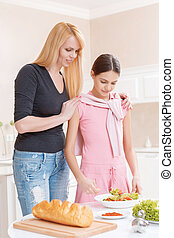 Mother and daughter cooking salad