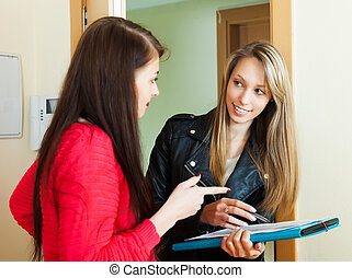 Woman answer questions of social worker with papers at door...