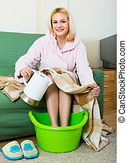 Blonde taking foot bath at home - Smiling young woman taking...