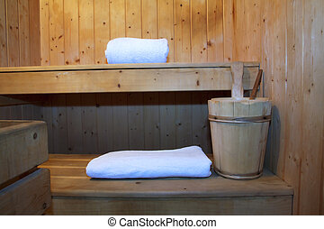 Sauna - Inside a wooden sauna, towel, candle and bucket