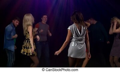 Girl the foreground dancing a silver dress. Happy young...