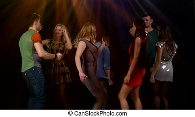 Group of friends talking while dancing to the music. Action takes place in a nightclub