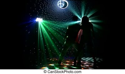 Girl and guy dancing in glow of LED spotlights. company...