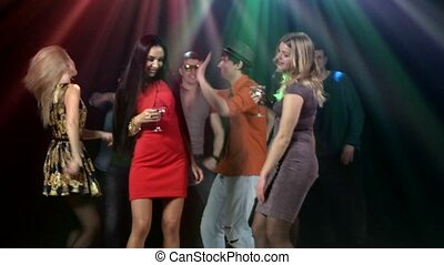 Group of friends at party dancing. Two girls the foreground dancing with a martini glass in hand
