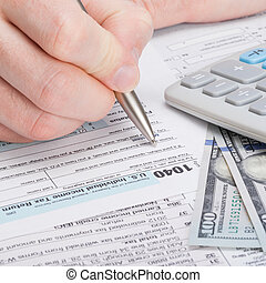 Taxpayer filling out USA 1040 Tax Form - close up studio...