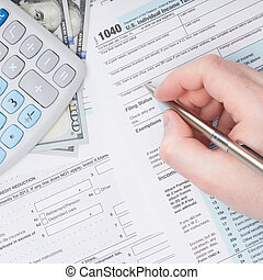 Filling out US 1040 Tax Form - close up studio shot -...