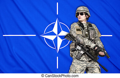 US soldier with gun on a Nato flag background