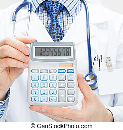 Male doctor holding calculator in hands - health care concept
