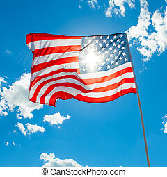 U.S. flag with cumulus clouds and blue sky on background
