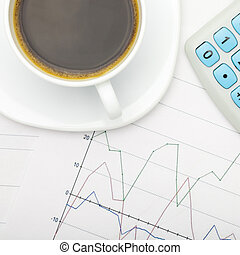 Coffee cup and calculator over stock market charts - close up studio shot