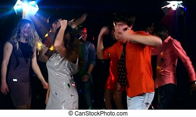 Pretty couple of young people dancing at a party in the...