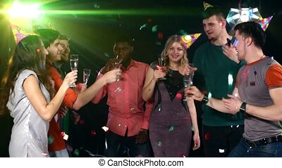 Nightclub : company of friends  party and dancing clink glasses.