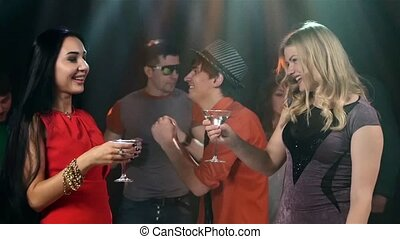 Group of friends at party dancing. Two girls the foreground dancing with a martini glass in hand. Slow motion