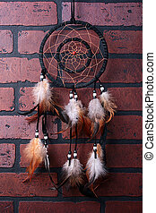 Dream catcher - On darkly brown brick wall hangs dream...
