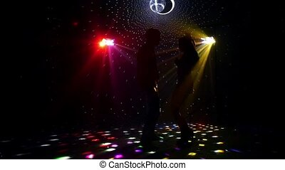 Girl and guy dancing in glow of LED spotlights. Slow motion...