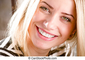 closeup picture of green eyes pinup girl beautiful blond young woman having fun happy smiling showing great dental whitening teeth & looking at camera