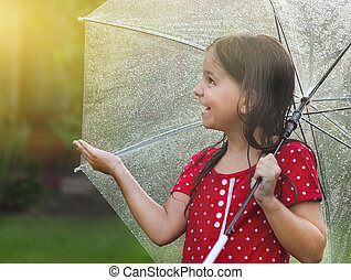 Child wearing polka dots dress under umbrella in rainy day