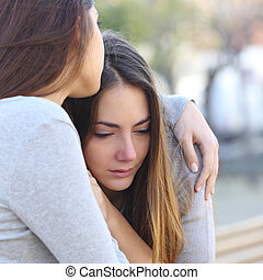 Sad girl crying and a friend comforting her outdoors in a...