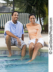 A happy African American man and woman couple in their thirties sitting wth their feet in a swimming pool