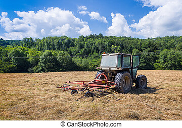Tractor with rotary rakes parked on dry grassland in Cazavet...