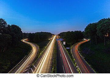 interchange at sunset lighttrails - A highway crossing at...