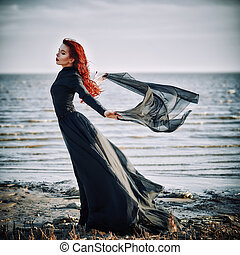 Beautiful sad goth girl with cloth in hands standing on sea...