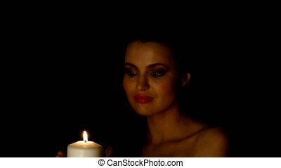 Woman with candle in dark room