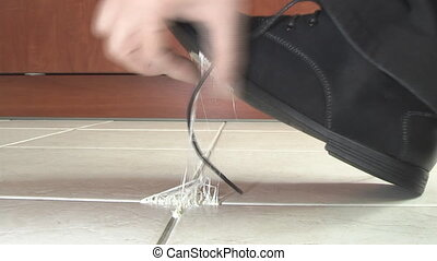 man removes chewing gum from the sole of his shoe