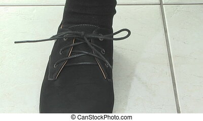 man unties shoelaces and takes off his shoes