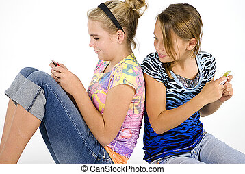 Sending Text Messages - Two pretty adolescent girls having...