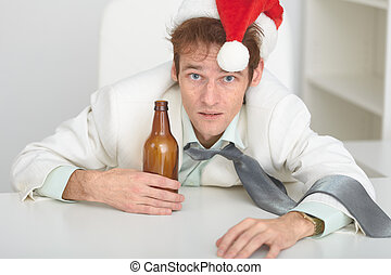 Young man in Christmas hat at office with a beer bottle