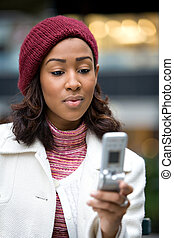 Business Woman Texting - A young woman text messaging or...