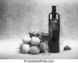 Black and white still-life with wine and fruit on sacking