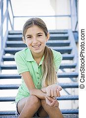 Portrait of Smiling Tween Girl Sitting On Stairway
